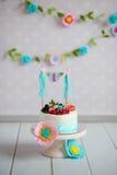 Gâteau d'anniversaire décoré des fruits et d'une guirlande Photos libres de droits