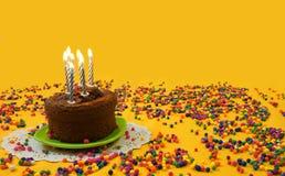 Gâteau d'anniversaire de chocolat avec les bougies bleues et blanches allumées, d'un petit plat vert entouré par des boules de su Photographie stock libre de droits