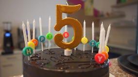 Gâteau d'anniversaire de chocolat avec les bougies et le numéro cinq clips vidéos