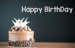 Gâteau d'anniversaire devant un tableau Mini gâteau Petit gâteau de chocolat avec la fourchette photo libre de droits
