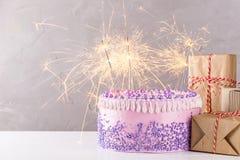 Gâteau d'anniversaire rose avec des cierges magiques et des boîte-cadeau Images libres de droits