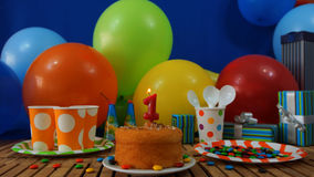 Gâteau d'anniversaire sur la table en bois rustique avec le fond des ballons colorés, des cadeaux, des tasses en plastique et du  Photos stock