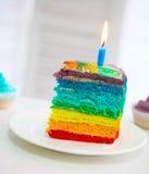 Gâteau d'arc-en-ciel décoré de la bougie d'anniversaire Photographie stock