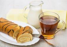 Gâteau de bûche dans le plat, le lait de cruche et le thé Images libres de droits
