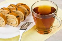 Gâteau de bûche dans le plat sur la serviette jaune, thé Image libre de droits