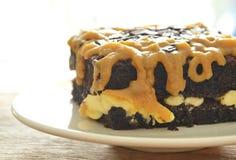 Gâteau de beurre de chocolat habillant la crème douce brune de caramel sur le plat images libres de droits