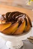 Gâteau de Bundt avec le lustre de sucre et de chocolat sur le fond blanc Photos stock