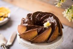 Gâteau de Bundt avec le lustre de sucre et de chocolat sur le fond blanc Photographie stock