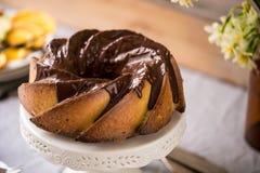 Gâteau de Bundt avec le lustre de sucre et de chocolat sur le fond blanc Photo stock