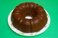 Gâteau de Bundt de chocolat d'isolement sur le fond vert photos stock