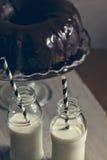 Gâteau de Bundt et deux bouteilles de lait avec des pailles Image libre de droits