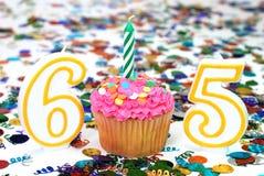 Gâteau de célébration avec la bougie - numéro 65 Images stock