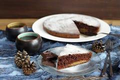 Gâteau de chocolat avec des cônes de pin et thé noir sur le tissu bleu Images stock