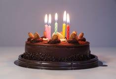 Gâteau de chocolat avec la bougie de lumière d'anniversaire Image stock