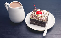 Gâteau de chocolat avec la cruche de cerise et de lait Image libre de droits