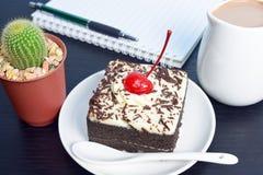 Gâteau de chocolat avec la cruche de cerise et de lait, cactus, carnet Photographie stock