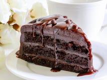 Gâteau de chocolat avec le beau bouquet des roses jaunes et d'une belle tasse de café Image stock