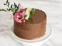 Gâteau de chocolat avec le givrage et les fleurs de chocolat Photos stock