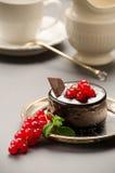 Gâteau de chocolat avec une groseille rouge sur un plat Photo stock