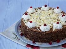 Gâteau de chocolat décoré des rosettes de crème et des baies sur un fond en bois Images libres de droits