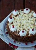Gâteau de chocolat décoré des rosettes de crème et des baies sur un fond en bois Images stock