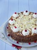 Gâteau de chocolat décoré des rosettes de crème et des baies sur un fond en bois Image stock