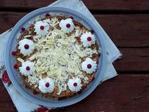 Gâteau de chocolat décoré des rosettes de crème et des baies sur un fond en bois Photographie stock libre de droits