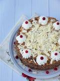 Gâteau de chocolat décoré des rosettes de crème et des baies sur un fond en bois Photographie stock