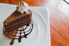 Gâteau de chocolat délicieux avec le wipcream du plat sur la table en bois Photos stock