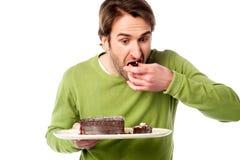 Gâteau de chocolat d'échantillon de jeune homme dans la hâte Photographie stock libre de droits
