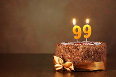 Gâteau de chocolat d'anniversaire avec les bougies brûlantes comme numéro quatre-vingt-dix-neuf Image stock