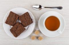 Gâteau de chocolat dans le plat, la cuillère à café, le sucre et la tasse de thé Photos libres de droits