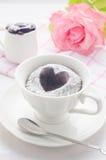 Gâteau de chocolat dans une tasse avec la fleur rose sur le backgro en bois blanc Photos stock