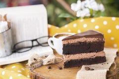 Gâteau de chocolat de mousse de café avec le livre, décoration en verre du plat en bois photographie stock