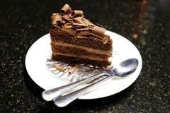 Gâteau de chocolat sur le plat avec la fourchette et la cuillère Image stock