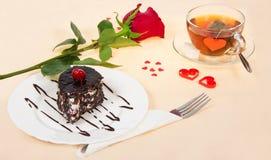 Gâteau de chocolat, thé chaud et rose de rouge Photo stock
