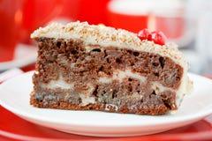 Gâteau de Cocolate avec des écrous. Sur un fond rouge. Photographie stock libre de droits