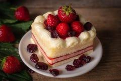 Gâteau de couche de fraise complétant la fraise mettant sur le plat blanc sur le fond en bois de table photo stock