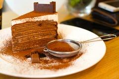 Gâteau de crêpe de chocolat avec du chocolat en poudre dans le plat blanc sur le Th Photo libre de droits