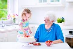 Gâteau de cuisson de grand-mère avec la petite-fille Images stock