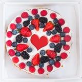 Gâteau de fête avec des baies et la forme de coeur Photographie stock