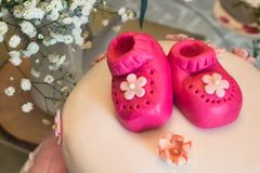 Gâteau de fête de naissance avec peu de butins roses de massepain pour une fille et un arrangement floral photographie stock libre de droits