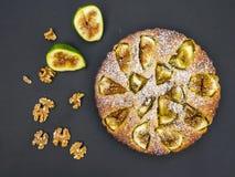 Gâteau de figue avec les figues et les noix fraîches sur le noir Photo stock