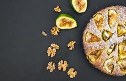 Gâteau de figue avec les figues et les noix fraîches sur le noir Photos stock