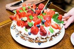 Gâteau de fraise avec des myrtilles dans la crème et des feuilles en bon état photographie stock