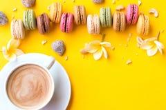 Gâteau de macaron et tasse de café français Macarons avec les fleurs blanches sur la configuration jaune d'appartement de fond image stock
