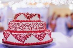 Gâteau de mariage avec la décoration rouge Photographie stock libre de droits