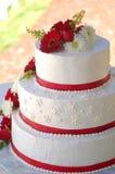 Gâteau de mariage avec les pistes et les fleurs rouges Images libres de droits