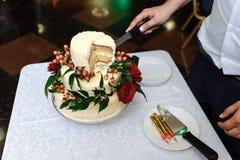Gâteau de mariage avec un morceau coupé sur une nappe blanche et une main d'un marié photos libres de droits