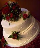 Gâteau de mariage blanc avec les roses rouges Photos libres de droits